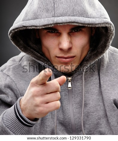 Closeup portrait of a threatening mafia man, over gray background, representing the concept of danger - stock photo