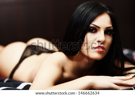Closeup portrait of a topless young woman in lingerie in the bedroom, on bed - stock photo