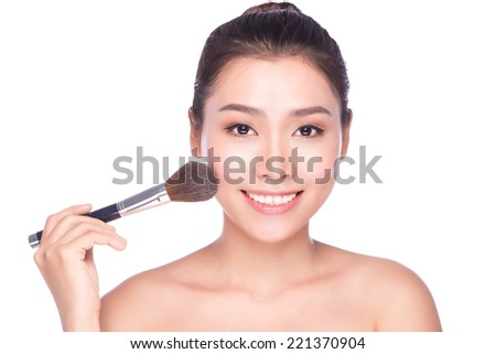 Closeup portrait of a woman applying dry cosmetic tonal foundation on the face using makeup brush.Beautiful woman with beauty face and perfect skin isolated on white background, asian model.  - stock photo