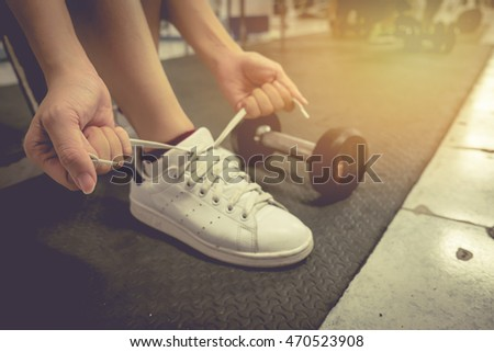 Closeup portrait of a woman hands tying shoelaces in gym. vintage.