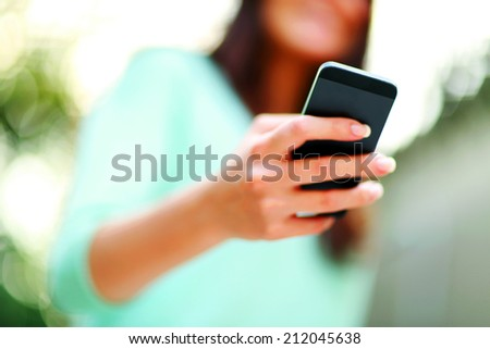 Closeup portrait of a woman using smartphone - stock photo