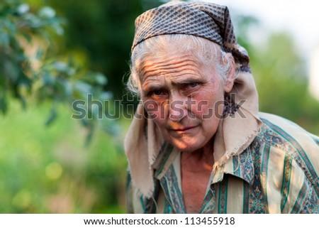 Closeup portrait of a worried senior woman, outdoors in a garden - stock photo