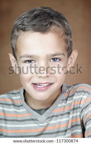 Closeup portrait of a 5 year old boy looking at the camera with beautiful eyes and smiling - stock photo