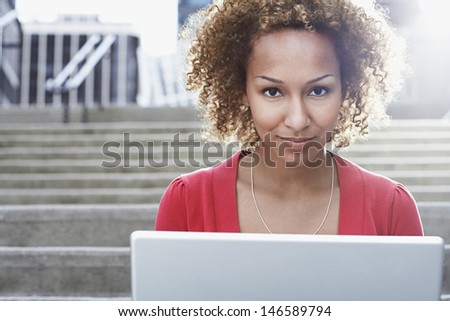 Closeup portrait of a young African American woman with laptop on steps outdoors - stock photo