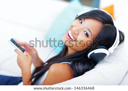 Closeup portrait of a young asian woman in headphones listening to music with her smartphone - stock photo