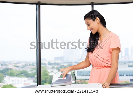 Closeup portrait of a young, attractive housewife, enjoying household work, ironing, engrossed, dignity of labor. Positive human emotions on isolated glass window indoor  background. - stock photo