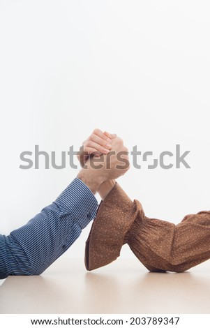 Closeup portrait of a young attractive woman and man fighting on hands isolated on white background