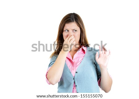 Closeup portrait of a young attractive woman who covers her nose, looks away, something stinks, isolated on white background - stock photo