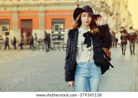 Closeup portrait of a young beautiful lady walking at street of  the old city. Model wearing stylish black fur coat and wide-brimmed hat. Girl looking aside. Female fashion concept. Toned  - stock photo
