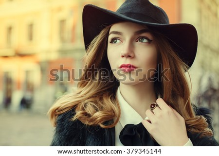 Closeup portrait of a young beautiful lady walking at street of  the old city. Model wearing stylish black fur coat and wide-brimmed hat. Girl looking up. Female fashion concept. Toned - stock photo
