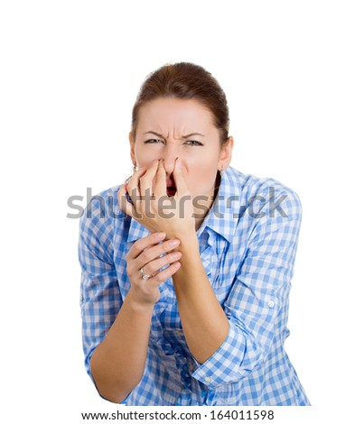 Closeup portrait of a young beautiful, unhappy woman who covers her nose, looks away, something stinks, very bad smell, situation, isolated on white background. Human facial expressions and emotions  - stock photo