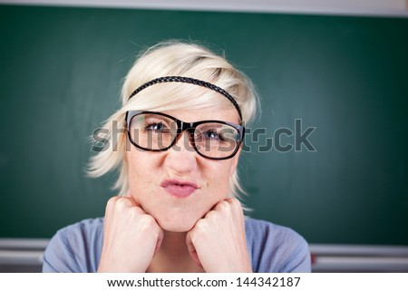 Closeup portrait of a young blond woman contorting her face against chalkboard
