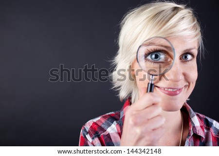 Closeup portrait of a young blond woman with magnifying glass against black background - stock photo