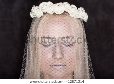 Closeup portrait of a young bride with her eyes closed. The veil and wreath of roses in her hair. The dark background - stock photo