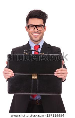 closeup portrait of a young business man presenting his briefcase with both his hands and smiling to the camera on a white background - stock photo