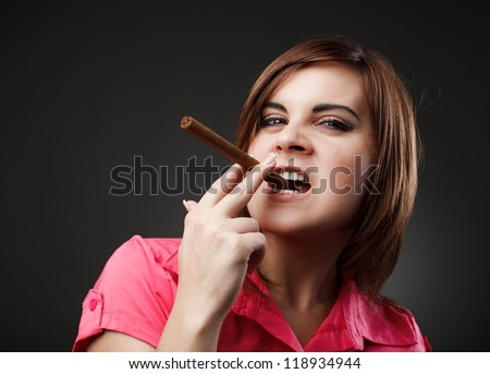Closeup portrait of a young businesswoman holding between her teeth - stock photo