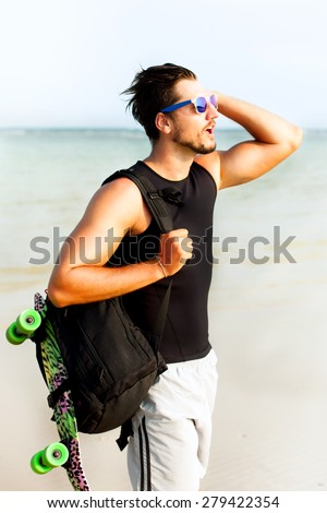closeup portrait of a young casual man looking away from the camera.Posing opposite the sea side at sunshine,enjoying beautiful view and relax near ocean.hiker,sportsman,Hipster style guy, sunset  - stock photo