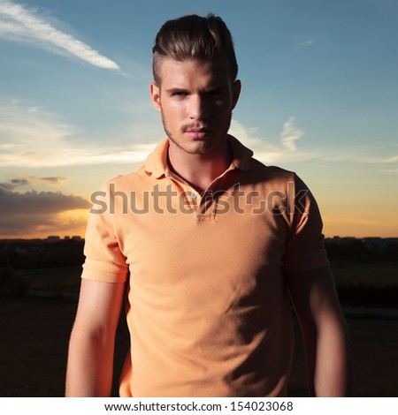 closeup portrait of a young casual man outdoor looking into the camera with the sunset behind