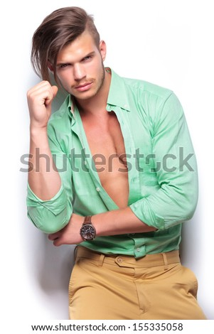 closeup portrait of a young casual man wearing an unbuttoned shirt, revealing his nice muscles, while looking into the camera. on white background