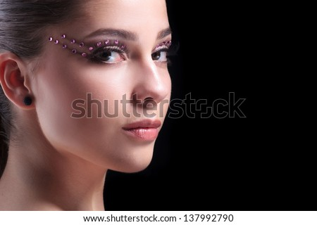 closeup portrait of a young casual woman with exotic makeup looking at the camera and showing a faint smile. on black background - stock photo