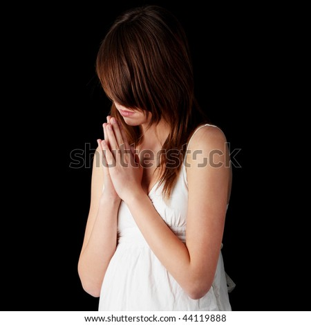 Closeup portrait of a young caucasian girl praying isolated on black background - stock photo