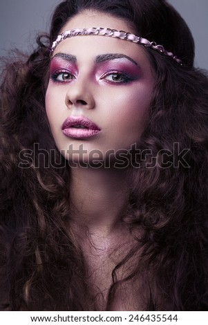 Closeup portrait of a young cute girl over grey background. Perfect bright makeup. Pink lips. Brunette with curly hair.  - stock photo