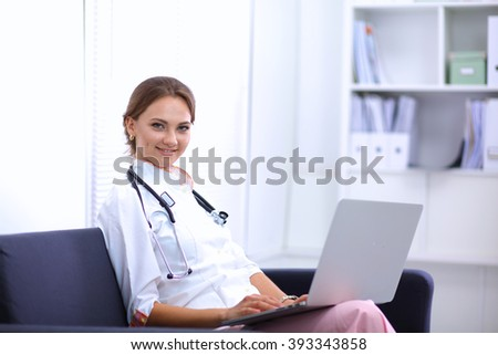 Closeup portrait of a young doctor sitting on the sofa