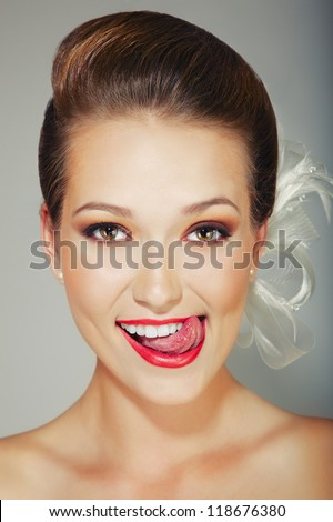 Closeup portrait of a young female with tongue licking lips - stock photo