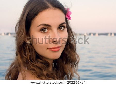 Closeup portrait of a young girl with a pink flower in hair on a beach near the water - stock photo