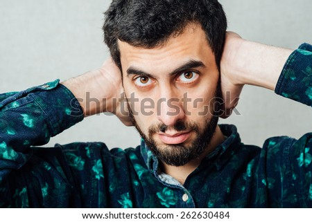 Closeup portrait of a young handsome beard man in shirt holding hands to ears covering to shut out noise looking  at neighbors - stock photo