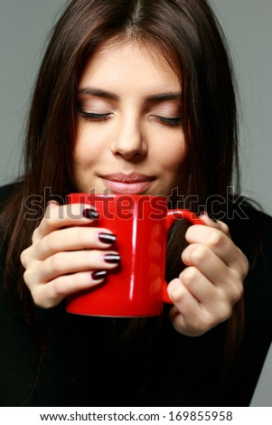 Closeup portrait of a young happy woman smelling the aroma of coffee - stock photo