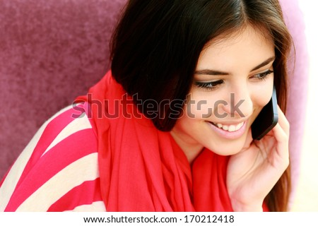 Closeup portrait of a young happy woman talking on the phone - stock photo