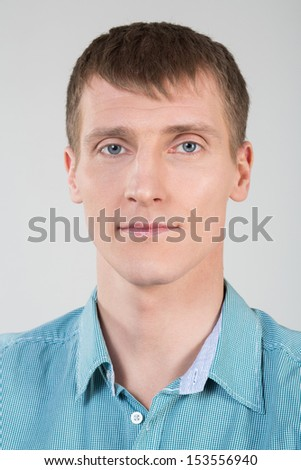 Closeup portrait of a young man in a shirt with blue eyes
