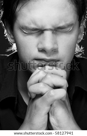 Closeup portrait of a young man praying to god - stock photo