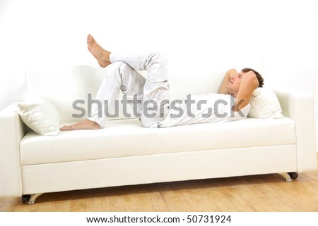 Closeup portrait of a young man resting on sofa at home - stock photo
