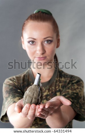 Closeup portrait of a young pretty female model holding out a mockup airsoft F-1 grenade, focus on the grenade