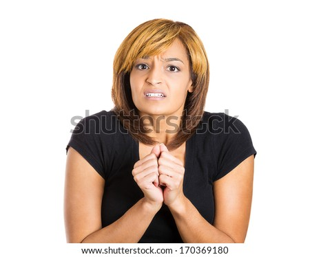 Closeup portrait of a young pretty woman hands fists up very anxious and tense in anticipation of something, isolated on white background. Negative human emotion facial expression feelings - stock photo