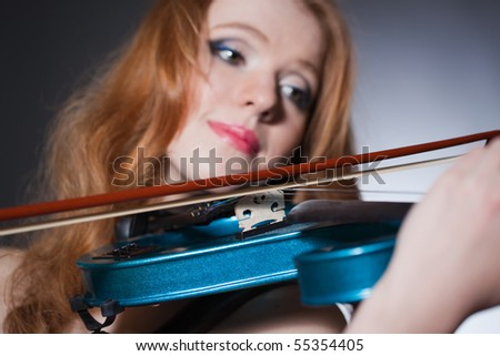 Closeup portrait of a young red-haired musician; unusual blue violin in focus