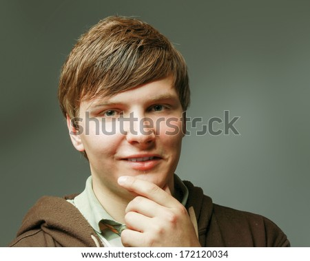 Closeup portrait of a young smiling guy, isolated on grey background - stock photo