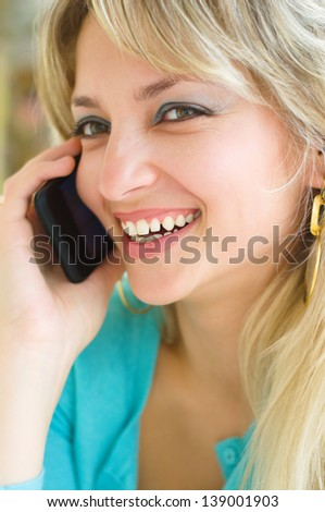 Closeup portrait of a young smiling pretty woman talking on mobile phone
