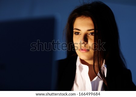 Closeup portrait of a young tired businesswoman working at night. Looking at laptop. - stock photo