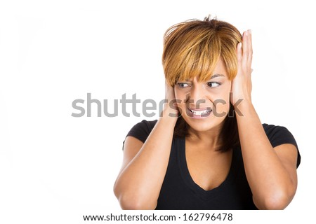 Closeup portrait of a young unhappy stressed woman covering her ears looking away, to say, stop making that loud noise it's giving me a headache, isolated on white background copy space to left - stock photo