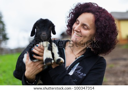 Closeup portrait of a young woman holding a baby goat outdoor