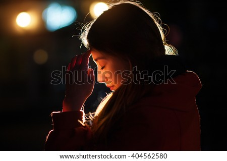 Closeup portrait of a young  woman praying - stock photo