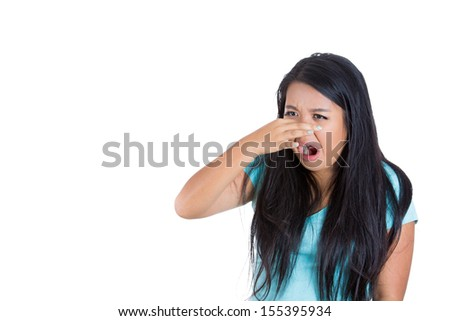 Closeup portrait of a young woman who covers her nose, looks away, something stinks, very bad smell, situation, isolated on white background - stock photo