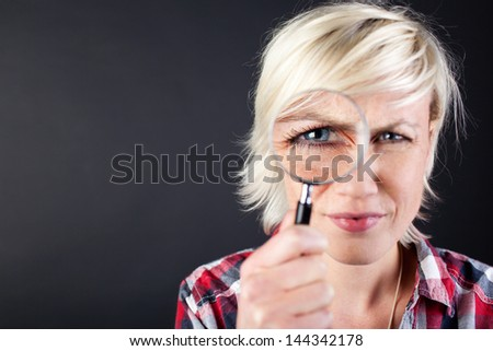 Closeup portrait of a young woman with magnifying glass against black background - stock photo