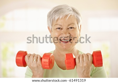 Closeup portrait of active senior woman doing dumbbell exercises at home, smiling.? - stock photo