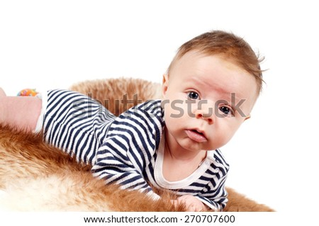 Closeup portrait of adorable baby boy lying on fur - stock photo