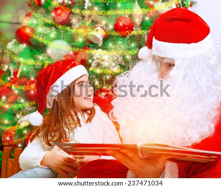 Closeup portrait of adorable baby girl with Santa Claus sitting near beautiful Christmas tree background and reading magical winter fairytale, happy childhood concept - stock photo