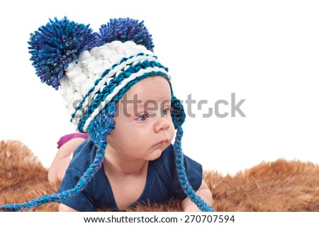 Closeup portrait of adorable baby in hat with pom-pom lying on fur - stock photo